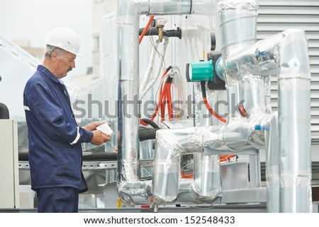 adult electrician engineer working with ventilation and conditioning system - stock photo
