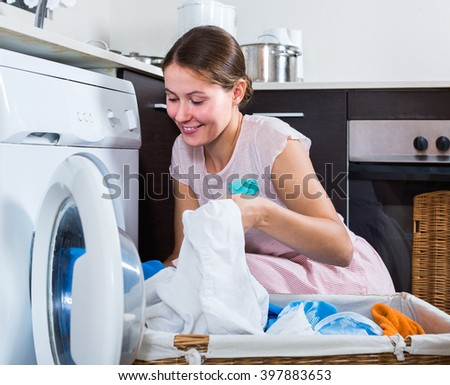 adult european housewife with basket of linen near washing machine indoors - stock photo