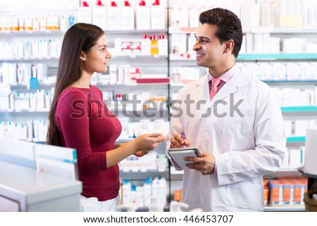 Adult experienced pharmacist counseling female customer - stock photo