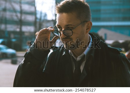 Adult fashion model looking aside through glasses outdoors - stock photo