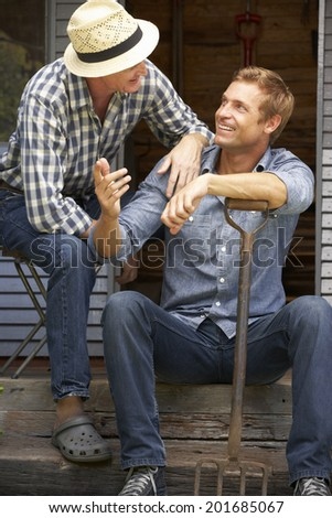 Adult father and son on veranda - stock photo