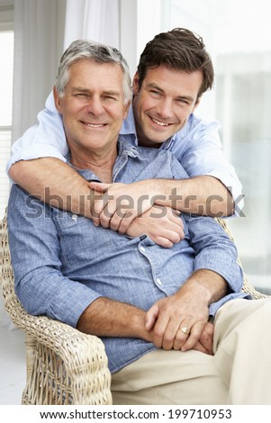 Adult father and son relaxing at home - stock photo
