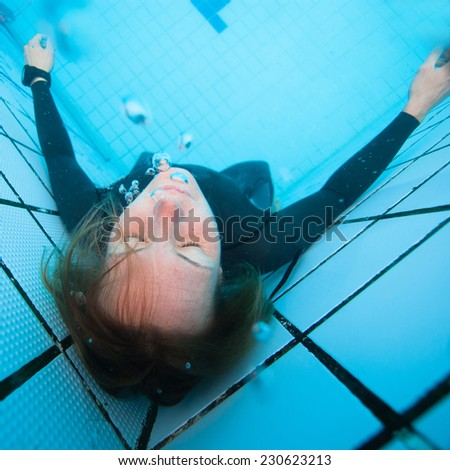 Adult female diver concentrating underwater with eyes closed in corner of swimming pool  - stock photo