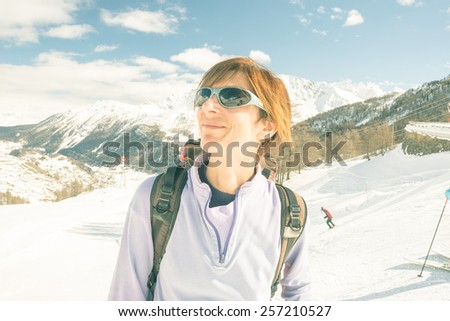Adult female skier with backpack and sunglasses showing happiness on a sunny day in the ski resort of La Thuile, Aosta Valley. Toned image, decontrasted. - stock photo