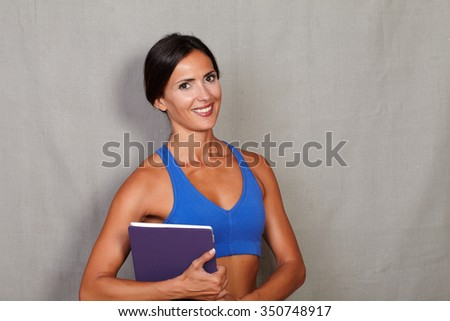 Adult female smiling and carrying tablet while looking at camera against grey texture background - stock photo