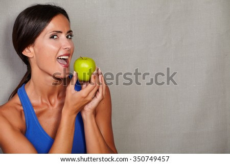 Adult female with open mouth holding apple and looking at camera on grey texture background - stock photo