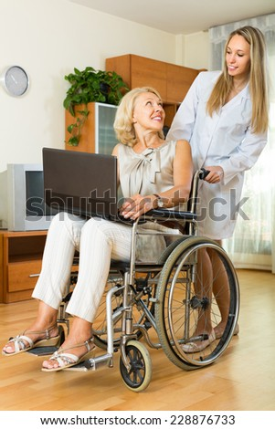 Adult girl and smiling handicapped mature woman with laptop indoor. Focus on mature - stock photo