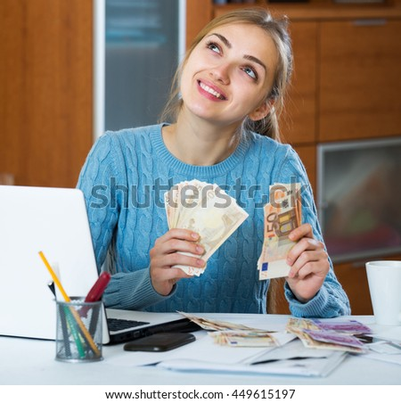 Adult girl sitting near laptop and counting money indoors - stock photo