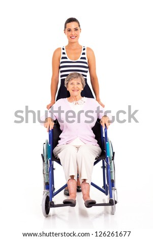 adult granddaughter pushing disabled senior grandmother on wheelchair - stock photo
