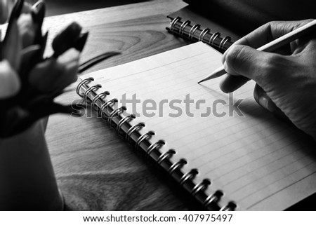 Adult hand hold pencil and writing on notebook, black and white tone with window light - stock photo