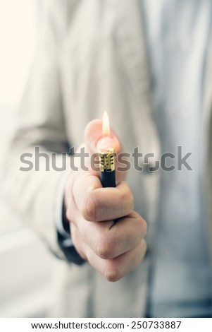 adult hand lighting a lighter and the warm flame - stock photo