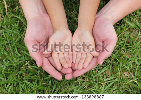 Adult hands holding kid hands with green grass background. - stock photo