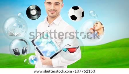 Adult handsome man holding tablet computer. Icons of different object are flying around. All multimedia in one mobile gadget concept - stock photo