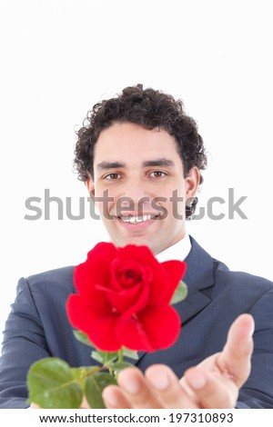 adult handsome smiling man in a suit holding a red rose and offers it to the camera to someone, focus on his face - stock photo