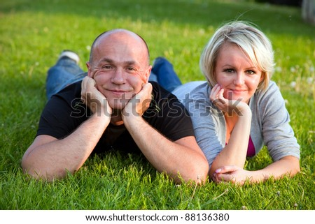 Adult happy couple together lying on grass - stock photo