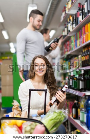 Adult happy european shoppers choosing bottle of wine at liquor store - stock photo