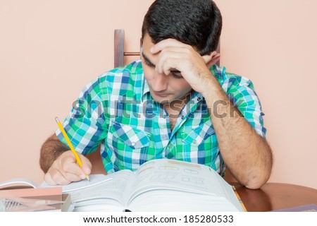 Adult hispanic man studying and writing on a notebook with a pile of books on his desk - stock photo