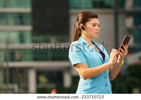 Adult hispanic person with mobile phone and wireless bluetooth headset, talking on telephone in the street out office buildings  - stock photo