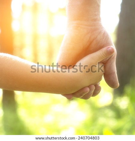 Adult holding a child's hand, close-up hands, nature in background.  - stock photo
