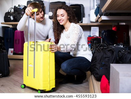 Adult husband and pretty wife selecting handy trunk in store - stock photo
