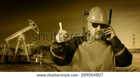 Adult industrial worker in glasses, with helmet camera, talking on radio transceiver, on a  oil field background. Toned sepia.  - stock photo