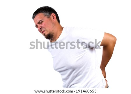 Adult male bends over in pain while rubbing his back. - stock photo