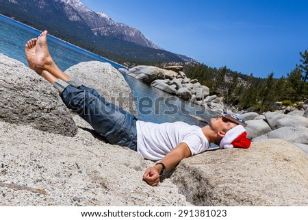 Adult male wearing a santa hat relaxing reading a book in Lake Tahoe - stock photo