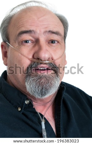 Adult male with an Oxygen hose to provide supplemental O2, due to a breathing disability such as emphysema or COPD. - stock photo