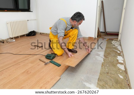 Adult male worker installing laminate floor,  floating wood tile - stock photo