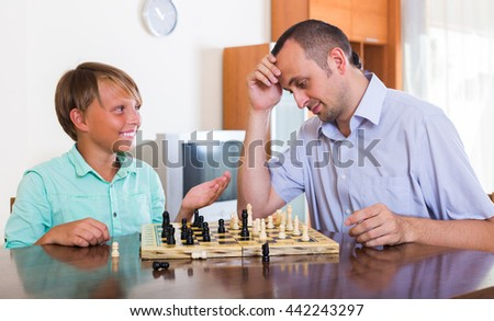 Adult man and cheerful teenager boy playing chess at home