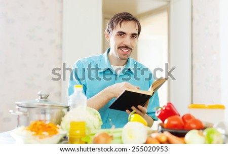 Adult man doing veggy lunch with cookbook at kitchen - stock photo