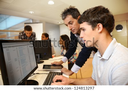 Adult man helping student in classroom - stock photo