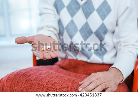 Adult man in wheelchair. Close up photo of man sitting in wheelchair and taking pills - stock photo