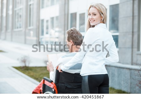 Adult man in wheelchair during walk. Young helper smiling and looking at camera. Nurse carrying patient on wheelchair. Back view photo - stock photo
