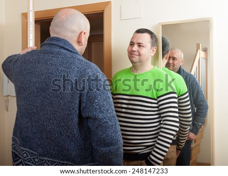 Adult man opening  door his neighbor - stock photo