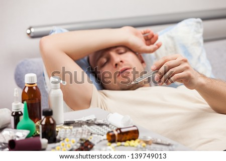 Adult man patient holding high temperature thermometer lying down bed for cold and flu illness relief - stock photo