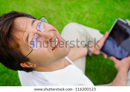 Adult man sitting on grass and using his tablet computer - stock photo