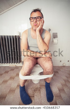 Adult man sitting on toilet bowl in restroom - stock photo