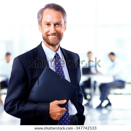 adult man smiling looking at the camera with a folder in his hands - stock photo