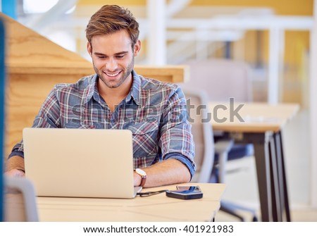 Adult man smiling while he works on his laptop - stock photo