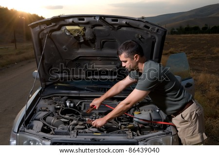 Adult man using jumper cables to start a car battery. - stock photo