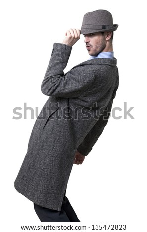 Adult man wearing an overcoat and lowering his hat a little in a greeting gesture. Standing sideways and looking to the lens, his knees bent and leaning back Isolated on white background. - stock photo
