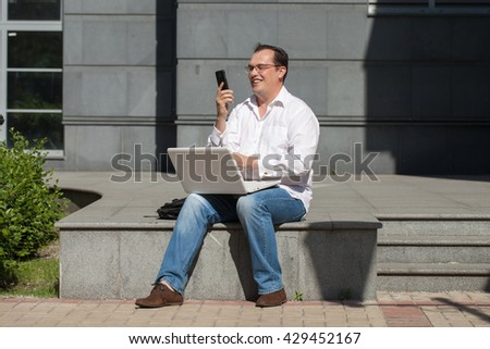 Adult man with computer and mobile phone sitting outdoors sunny day - stock photo