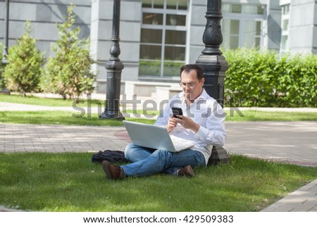 Adult man with laptop and mobile phone sitting on the grass - stock photo