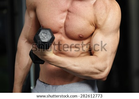 Adult man with weight training equipment on sport modern gym - stock photo