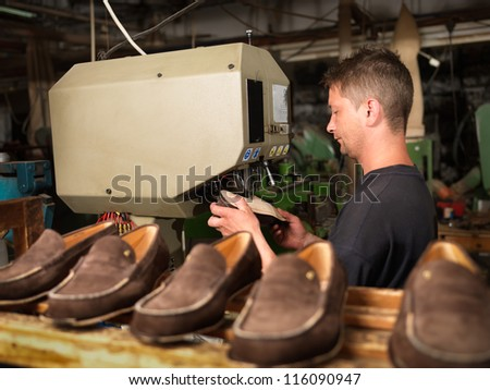 adult man working in a shoe factory, sewing the soles of the shoes, at a machine - stock photo