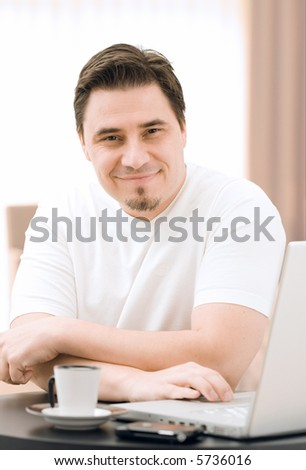 Adult man working on laptop computer at home - stock photo