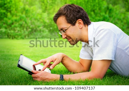 Adult man working with tablet computer outdoor in park - stock photo