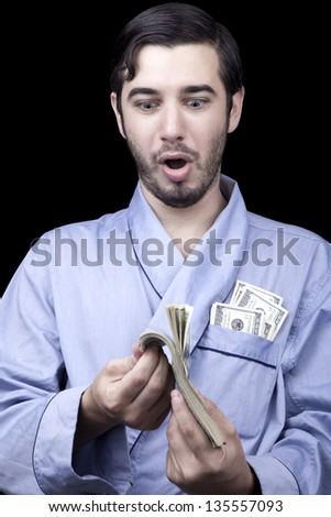Adult man (30 years old) appears to be quite a bum, looking down with an awed & surprised expression at a stack of 100 US$ bills that he's fluttering in his hands. Isolated on black background. - stock photo