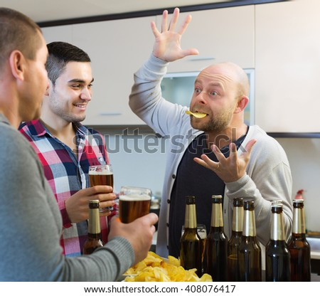 Adult men relaxing with beer and smiling in kitchen - stock photo